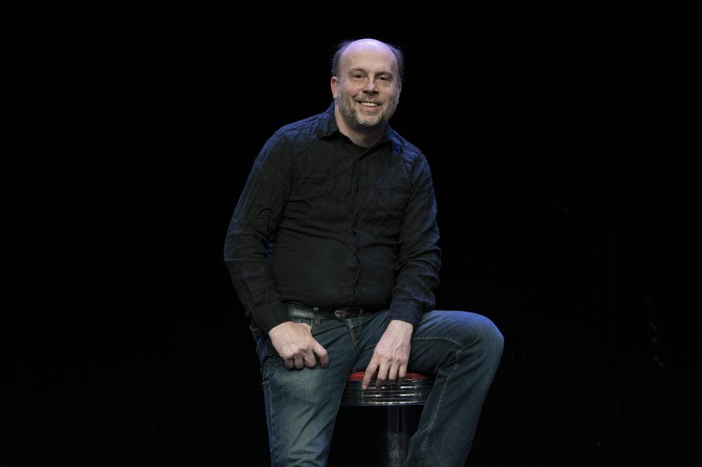 portrzit de Stéphan Meynet : sur fond noir, assis sur un tabouret